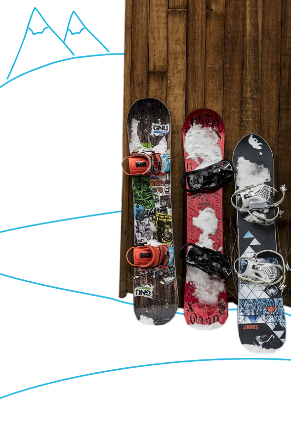 A row of snowboards leant up against a wooden building